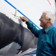 The senior man happy painting on the side of a sailboat.