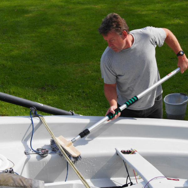 Middle aged man cleaning his dingy boat in his back yard after a day's sailing